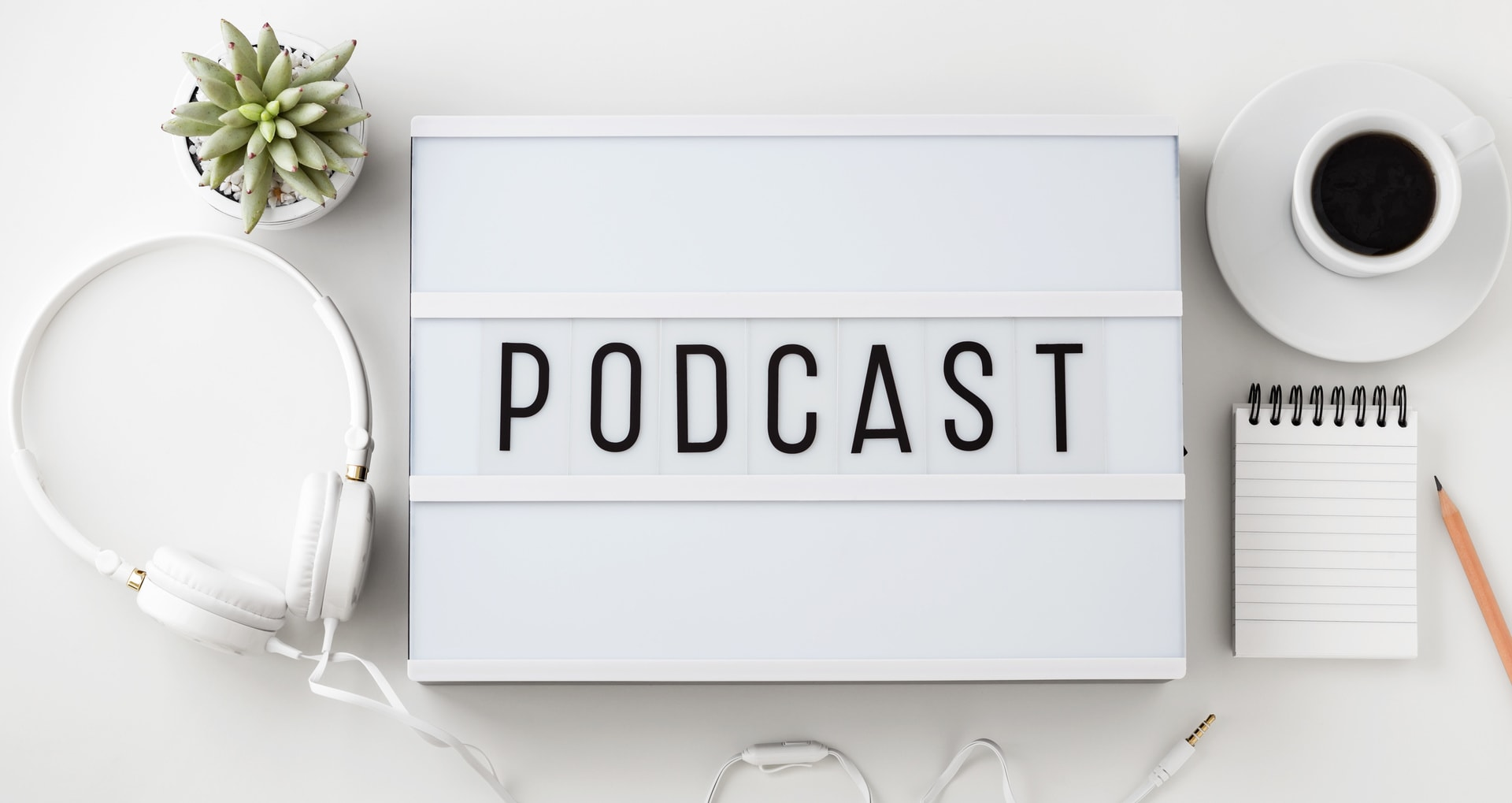 Podcast word on lightbox with headphones, coffee cup and notepad on white background, flat lay
