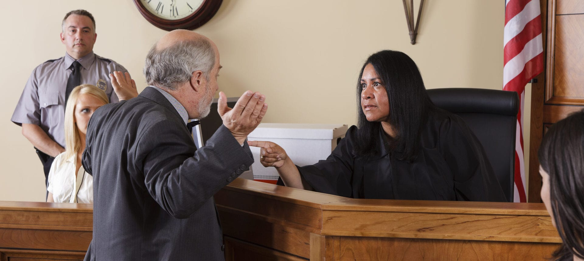 A lawyer talking to the judge in a courtroom.